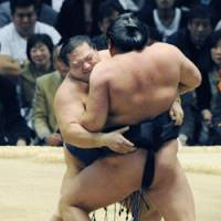 Strong grip: Ozeki Kaio shoves komusubi Kyokutenho out of the ring on the seventh day of the Spring Grand Sumo Tournament on Saturday in Osaka. | KYODO PHOTO