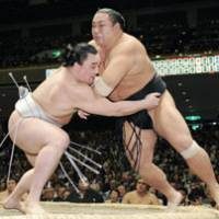 Staying undefeated: Ozeki Harumafuji forces out fellow ozeki Chiyotakai to stay undefeated with an 8-0 record on Sunday at Ryogoku Kokugikan. | KYODO PHOTO