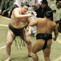 Man in charge: Yokozuna Hakuho shoves Chiyotaikai out of the ring on the 10th day of the Summer Grand Sumo Tournament at Ryogoku Kokugikan on Tuesday. | KYODO PHOTO