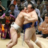 In control: Harumafuji eases Iwakiyama over the bales on the second day of the Nagoya Grand Sumo Tournament on Monday. | KYODO PHOTO