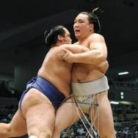 Big step back: Harumafuji (right) faces off against Kotoshogiku during the Nagoya Grand Sumo Tournament on Tuesday. The promotion-chasing Ozeki lost the bout. | KYODO PHOTO