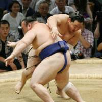 Forceful action: Yokozuna Asashoryu slaps Iwakiyama down on the seventh day of the Nagoya Grand Sumo Tournament on Saturday. | KYODO PHOTO