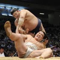 Three strikes: Kotomitsuki twists down Harumafuji on Day 9 of the Nagoya Basho, dashing all hopes of his promotion to yokozuna. | KYODO PHOTO