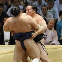 Out you go: Yokozuna Asashoryu manhandles ozeki Kotomitsuki during 12th day of the Nagoya Grand Sumo Tournament. | KYODO PHOTO