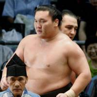 Leading the way: Hakuho walks in front of beaten opponent Kotooshu at the Nagoya Grand Sumo Tournament on Friday. | KYODO PHOTO