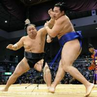 Talk to the hand: Chiyotaikai thrusts a blow to the face of Kakuryu at the Kyushu Grand Sumo Tournament on Monday. | KYODO PHOTO