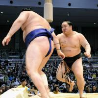 All-Mongolian battle: Yokozuna Asashoryu forces out No. 2 maegashira and fellow-Mongolian Tokitenku to stay undefeated on Wednesday at Fukuoka Kokusai Center. | KYODO PHOTO