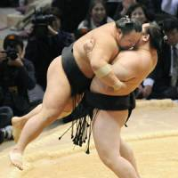 A little heavy lifting: Asashoryu picks up Chiyotaikai during their bout at the Kyushu Grand Sumo Tournament on Tuesday. | KYODO PHOTO