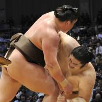 Wrapping up the championship: Hakuho (left) defeats ozeki Kotomitsuki to clinch the Emperor's Cup on Saturday. | KYODO PHOTO