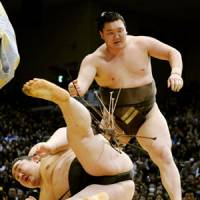 Last man standing: Hakuho downs Asashoryu to finish with a perfect record at the Kyushu Grand Sumo Tournament on Sunday. | KYODO PHOTO