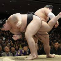 Going down: Asashoryu teeters over the edge of the ring before losing to Goeido at the New Year Grand Sumo Tournament on Thursday. | KYODO PHOTO