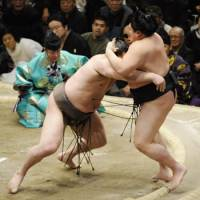 Show of force: Yokozuna Hakuho (left) overpowers Hokutoriki on Friday during the New Year Grand Sumo Tournament. Hakuho is the only remaining unbeaten wrestler in the 15-day tournament. | KYODO PHOTO