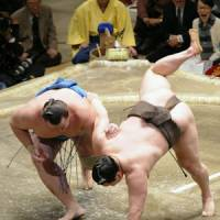 On the offensive: Baruto (left) outduels Mongolian yokozuna Hakuho on Saturday in the New Year Grand Sumo Tournament at Tokyo's Ryogoku Kokugikan. | KYODO PHOTO