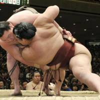 Bouncing back: Hakuho (left) hauls down Kisenosato at the New Year Grand Sumo Tournament on Sunday. | KYODO PHOTO