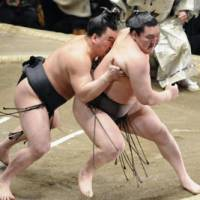 Upset special: Harumafuji pushes Hakuho out of the ring at the New Year Grand Sumo Tournament. | KYODO PHOTO