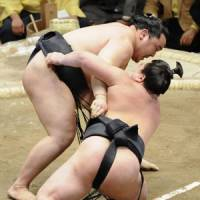 No surprise: Yokozuna Asashoryu (left) defeats Mongolian compatriot Harumafuji on Saturday in the New Year Grand Sumo Tournament. | KYODO PHOTO