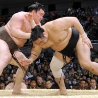 On with the show: Yokozuna Hakuho gets the better of komusubi Aminishiki on the first day of the Spring Grand Sumo Tournament in Osaka on Sunday. | KYODO PHOTO