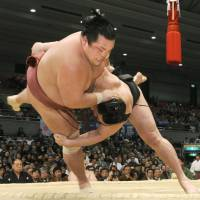 Show of strength: Ozeki Harumafuji (bottom) defeats Toyohibiki on Tuesday in the Spring Grand Sumo Tournament in Osaka. | KYODO PHOTO