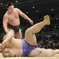 Still unbeaten: Hakuho (13-0) overpowers ozeki Kaio on Friday in the Spring Grand Sumo Tournament in Osaka. | KYODO PHOTO