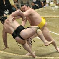 Perfect run: Summer Grand Sumo Tournament winner and yokozuna Hakuho shoves ozeki Kotooshu on the 14th day of the basho on Saturday at Ryogoku Kokugikan. | KYODO PHOTO