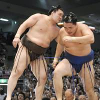 Another one bites the dust: Hakuho eases Kakuryu out of the ring on Monday. | KYODO PHOTO