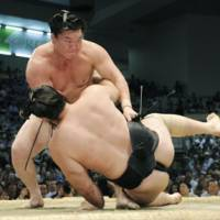Powerful shove: Yokozuna Hakuho (right) downs ozeki Kotooshu on the 13th day of the Nagoya Grand Sumo Tournament on Friday. With the win, the Mongolian tied former yokozuna great Taiho's 45-bout winning streak. | KYODO PHOTO