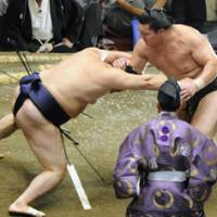 Move aside: Yokozuna Hakuho, right, tussles with Tokitenku at the Autumn Grand Sumo Tournament. | KYODO PHOTO