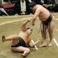Flat out: Hakuho hurls Kyokutenho to the ground at the Autumn Grand Sumo Tournament in Tokyo on Sunday. | KYODO PHOTO