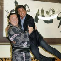 Light-hearted moment: Yokozuna Hakuho holds up actor Sylvester Stallone during a photo shoot on Saturday. | KYODO PHOTO