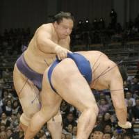 Strictly business: Kaio (left) demonstrates his strength in a victory over Kakuryu during the Kyushu Grand Sumo Tournament on Friday in Fukuoka. | KYODO PHOTO