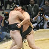 Weekend warrior: Hakuho (right) eases Aran out of the ring at the Kyushu Grand Sumo Tournament on Sunday. | KYODO PHOTO