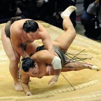 Balance of power: Hakuho throws Toyonoshima to win a playoff at the Kyushu Grand Sumo Tournament on Sunday. | KYODO PHOTO
