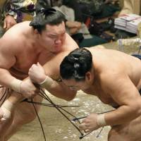 Wing and a prayer: Hakuho locks onto Kakuryu's arm on his way to victory on the first day of the New Year Grand Sumo Tournament in Tokyo on Sunday. | KYODO PHOTO
