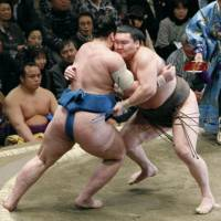 Brute force: Hakuho and rank-and-filer Tamawashi (left) square off on the eighth day of the New Year Grand Sumo Tournament at Ryogoku Kokugikan. | KYODO PHOTO