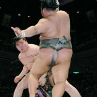 Putting on a show: Hakuho sends Toyonoshima reeling backward at Ryogoku Kokugikan on Sunday. | KYODO