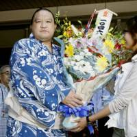 Man on top: Kaio receives a bouquet after winning his record 1,046th career match on Thursday at the Nagoya Grand Sumo Tournament. | KYODO PHOTO