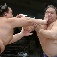Turn the other cheek: Kisenosato thrusts a hand into Kaio's face at the Nagoya Grand Sumo Tournament on Friday. | KYODO
