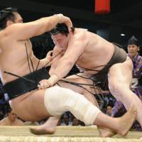 Show of force: Hakuho (right) manhandles Aminishiki at the Nagoya Grand Sumo Tournament on Sunday. | KYODO