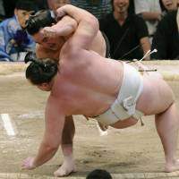 Dumped: Harumafuji tosses Baruto out of the ring during their bout at the Nagoya Grand Sumo Tournament on Friday. | KYODO PHOTO