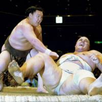 Sheer force: Hakuho (left) defeats Baruto on Saturday in the Autumn Grand Sumo Tournament at Ryogoku Kokugikan. | KYODO PHOTO