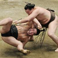 Master at work: Hakuho flips Harumafuji to the ground on the final day of the Autumn Grand Sumo Tournament at Tokyo's Ryogoku Kokugikan on Sunday. | KYODO