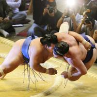 Flying start: Ozeki debutant Kotoshogiku tosses Tochinoshin outside the dohyo on Sunday, the first day of the Kyushu Grand Sumo Tournament. | KYODO PHOTO