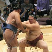 Getting the job done: Kisenosato (right) pushes Homasho out of the raised ring on Wednesday in the Kyushu Grand Sumo Tournament. | KYODO PHOTO