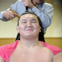 Taking it easy: Hakuho has his mage adjusted after his win at the Kyushu Grand Sumo Tournament | KYODO PHOTO