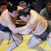 Power and patience: Yokozuna Hakuho (right) forces Harumafuji out of the ring on the 14th day of the Kyushu Grand Sumo Tournament in Fukuoka. | KYODO PHOTO
