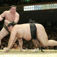 Start as you mean to go on: Hakuho (left) takes down Wakakoyu at the New Year Grand Sumo Tournament at Ryogoku Kokugikan on Sunday. | KYODO
