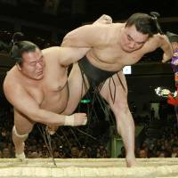 Brothers in arms: Harumafuji (right) throws Toyonoshima at the New Year Grand Sumo Tournament on Monday. | KYODO
