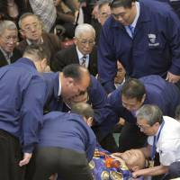 Referee injured in fall; Hakuho wins