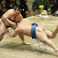 Head first: Kisenosato takes down Okinoumi at the New Year Grand Sumo Tournament on Sunday. | KYODO