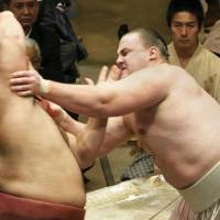 Going strong: Baruto (right) gets to grips with Takayasu at the New Year Grand Sumo Tournament on Monday. | KYODO